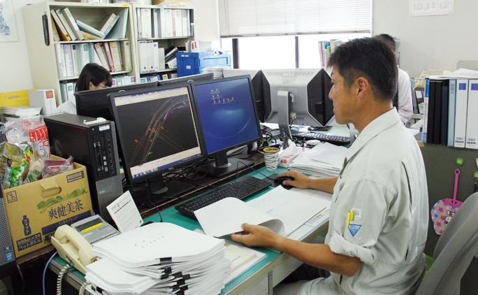 パソコン上で用水路の設計を行う馬渕さん。デスクワーク中心だそうで、休日はサッカーでリフレッシュしている。