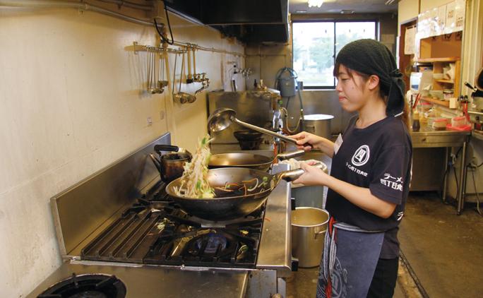 十勝ラーメン四丁目食堂で調理をする杉本ゆかりさん。女性も多く、活気がある。