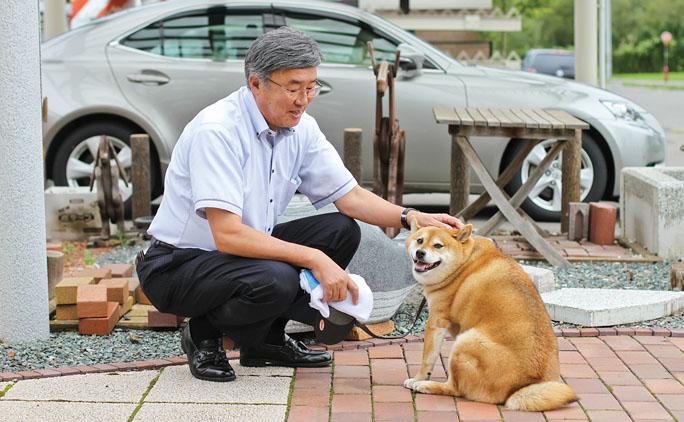 来海社長と愛犬、勘太郎(7歳)。勘太郎は1歳頃から社長の車の助手席に乗り毎日出社。社長宅の猫のエサを食べて少々太り気味。