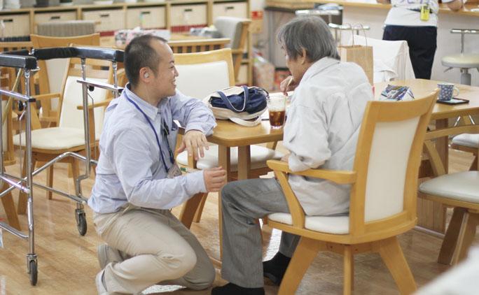デイサービスさくら内の「カフェ憩」でくつろぐ男性に、スタッフの掘真太朗さんが寄り添う。